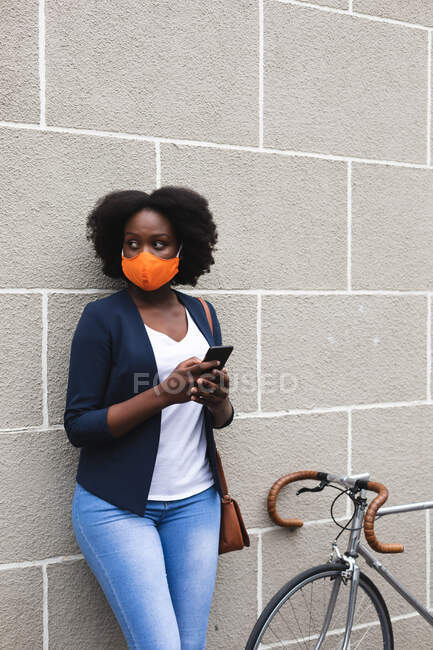 African american woman wearing face mask using smartphone in street out and about in the city during covid 19 coronavirus pandemic. — Stock Photo