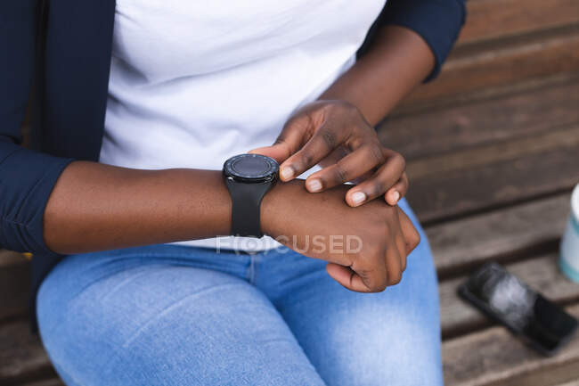 African american woman in street sitting on a bench, checking her smartwatch, out and about in the city during covid 19 coronavirus pandemic. — Stock Photo
