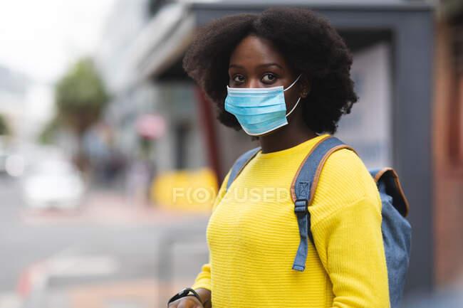 Портрет афро-американської жінки, одягненої в маску обличчя на вулиці і по всьому місту під час пандемії коронавірусу 19. — стокове фото