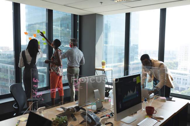 Различные коллеги в масках для лица приклеивают заметки на стеклянное окно в современном офисе, социальная изоляция карантина во время пандемии коронавируса — стоковое фото