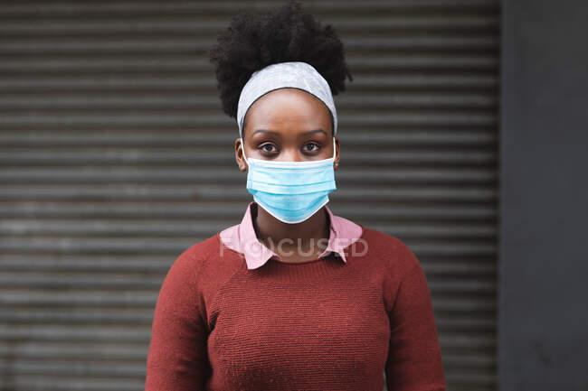 Portrait d'une femme afro-américaine regardant la caméra dans la ville pendant une pandémie de coronavirus 19. — Photo de stock