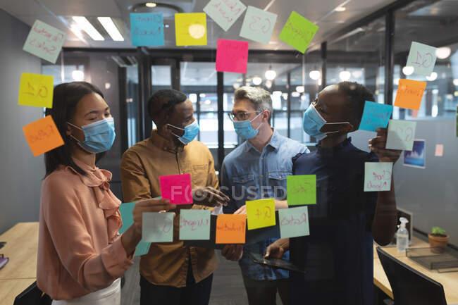 Разнообразные коллеги по офису в масках обсуждают заметки на стеклянной доске в современном офисе. социальная изоляция от карантина во время пандемии коронавируса — стоковое фото