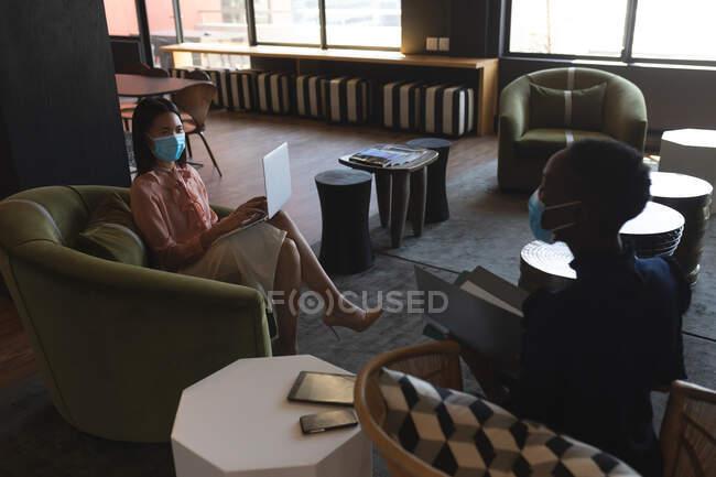 Donna asiatica che indossa maschera facciale utilizzando il computer portatile in ufficio moderno. isolamento di quarantena a distanza sociale durante la pandemia di coronavirus — Foto stock