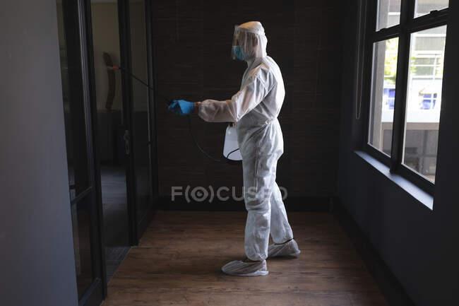 Gesundheitshelfer in Schutzkleidung reinigen Büro mit Desinfektionsmittel. Reinigung und Desinfektion Prävention und Kontrolle der Covid-19-Epidemie — Stockfoto