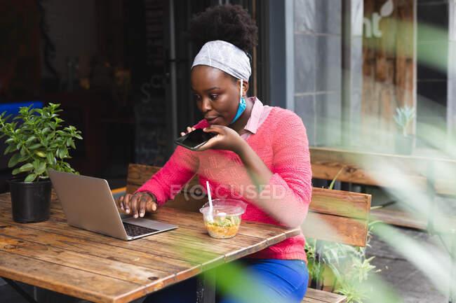 Африканская американка, сидящая в кафе с ноутбуком, разговаривающая по телефону и поедающая салат в городе во время пандемии коронавируса 19. — стоковое фото