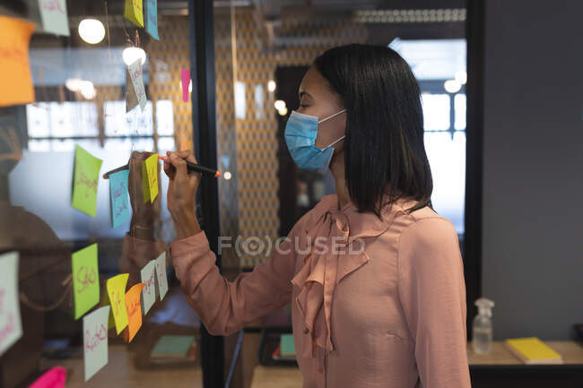 Азійка носить маску з маркером на скляній дошці в сучасному офісі. Відстань до карантину під час пандемії коронавірусу — стокове фото