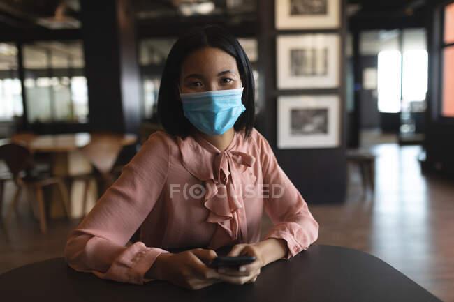 Портрет азійської жінки, одягненої в маску обличчя, тримає смартфон в сучасному офісі. Відстань до карантину під час пандемії коронавірусу — стокове фото