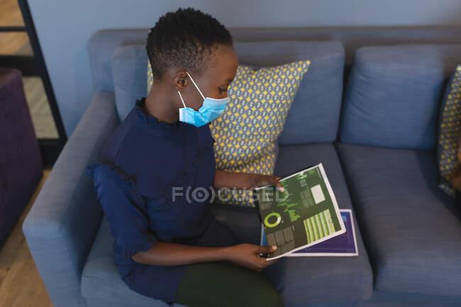 Mulher afro-americana usando máscara facial lendo documentos no escritório moderno. bloqueio de quarentena por distanciamento social durante a pandemia do coronavírus — Fotografia de Stock
