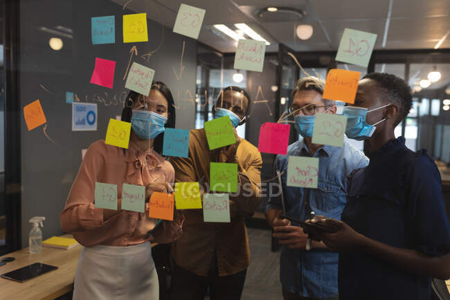 Разнообразные коллеги по офису в масках для лица устроили мозговой штурм. обсуждая заметки на стеклянной доске в современном офисе. гигиена на рабочем месте во время пандемии коронавируса — стоковое фото