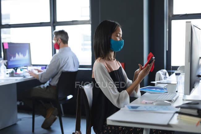Азиатка в маске для лица чистит смартфон, сидя на столе в современном офисе. гигиена и социальное дистанцирование на рабочем месте во время пандемии коронавируса 19. — стоковое фото