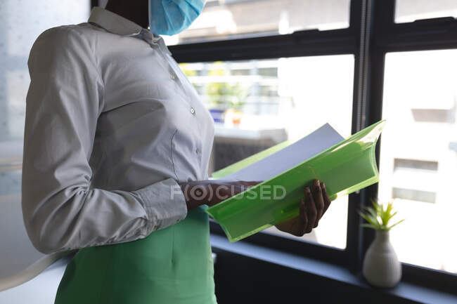 Seção intermediária de mulher usando máscara facial arquivo de leitura de documentos no escritório moderno. bloqueio de quarentena por distanciamento social durante a pandemia do coronavírus — Fotografia de Stock
