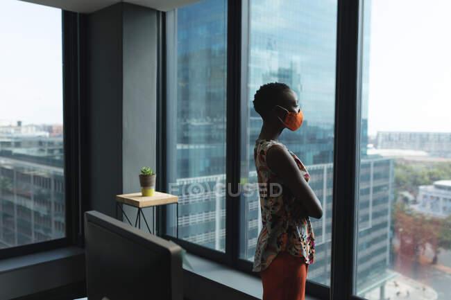 Африканська американка, одягнена в маску обличчя, дивиться у вікно в сучасному офісі. Відстань до карантину під час пандемії коронавірусу — стокове фото