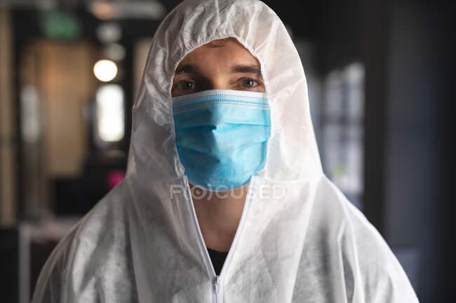 Porträt eines männlichen Gesundheitshelfers mit Mundschutz und Schutzkleidung im modernen Büro. Reinigung und Desinfektion Prävention und Kontrolle der Covid-19-Epidemie — Stockfoto