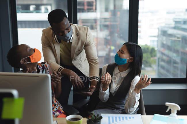 Різні колеги, які носять маску обличчя, сміються разом у сучасному офісі. гігієна і соціальна дистанція на робочому місці під час коронавірусу covid 19 пандемії. — стокове фото