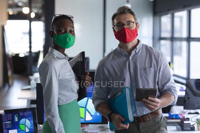 Porträt diverser männlicher und weiblicher Kollegen mit Gesichtsmasken im modernen Büro. Soziale Distanzierung von Quarantäne während der Coronavirus-Pandemie — Stockfoto