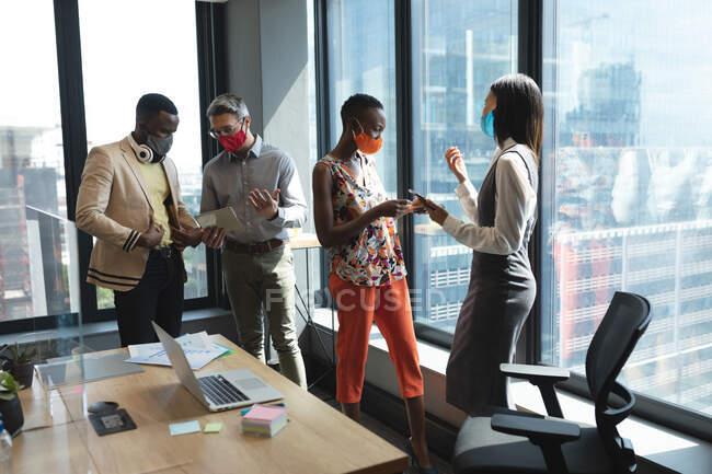 Diversi colleghi che indossano maschere facciali discutono insieme in un ufficio moderno. isolamento di quarantena a distanza sociale durante la pandemia di coronavirus — Foto stock