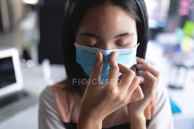 Primo piano di donna asiatica con la maschera che si tocca il naso in un ufficio moderno. isolamento di quarantena a distanza sociale durante la pandemia di coronavirus — Foto stock