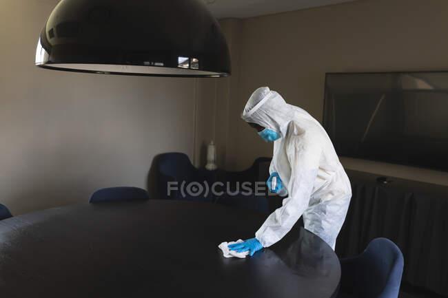 Trabalhador de saúde vestindo roupas de proteção escritório de limpeza usando spray desinfetante e pano. limpeza e desinfecção prevenção de infecção e controle da epidemia de covid-19 — Fotografia de Stock