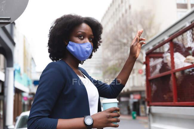 Afroamerikanerin mit Gesichtsmaske hält auf der Straße eine Tasse Kaffee und hebt die Hand. Während der 19-jährigen Coronavirus-Pandemie in der Stadt unterwegs. — Stockfoto