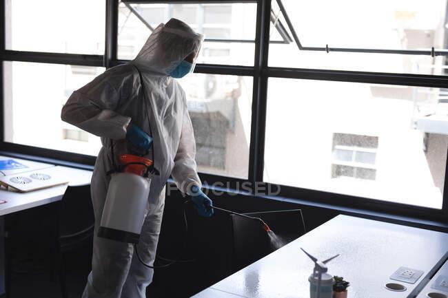 Trabalhador de saúde vestindo roupas de proteção escritório de limpeza usando desinfetante. limpeza e desinfecção prevenção de infecção e controle da epidemia de covid-19 — Fotografia de Stock