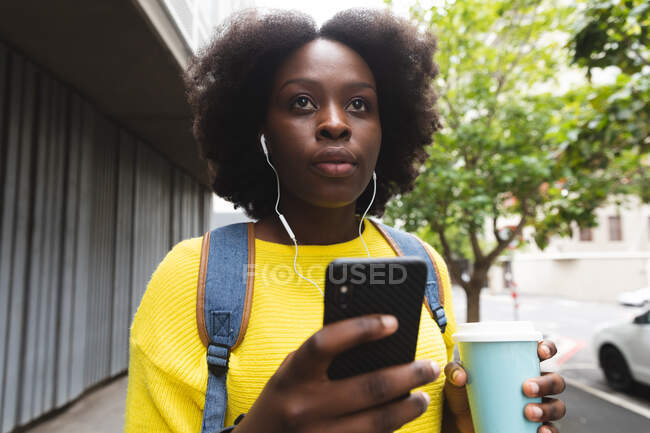 African american woman using smartphone on a street listening to music with earphones in. out and about in the city during covid 19 coronavirus pandemic. — Stock Photo