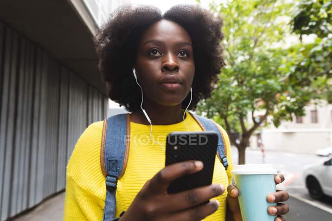 Африканская американка использует смартфон на улице, слушая музыку в наушниках. в городе во время 19 пандемических коронавирусов. — стоковое фото