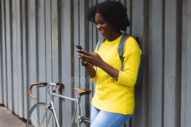 African american woman using smartphone on a street out and about in the city during covid 19 coronavirus pandemic. — Stock Photo