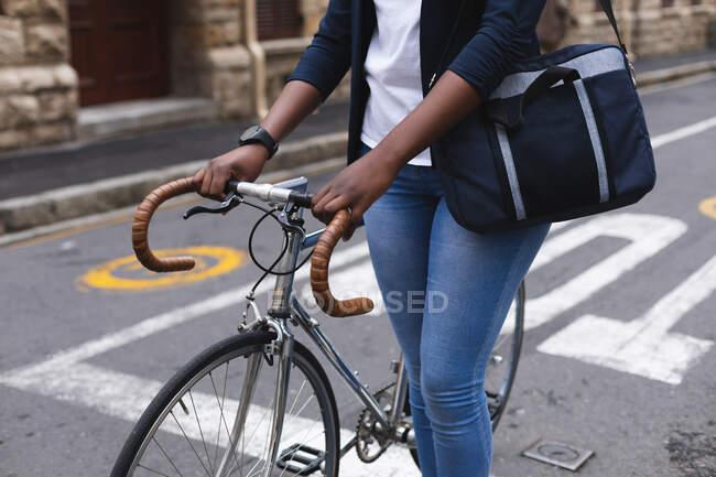 Africano americano mulher na rua andando e carregando sua bicicleta para fora e sobre na cidade durante covid 19 coronavirus pandemia. — Fotografia de Stock