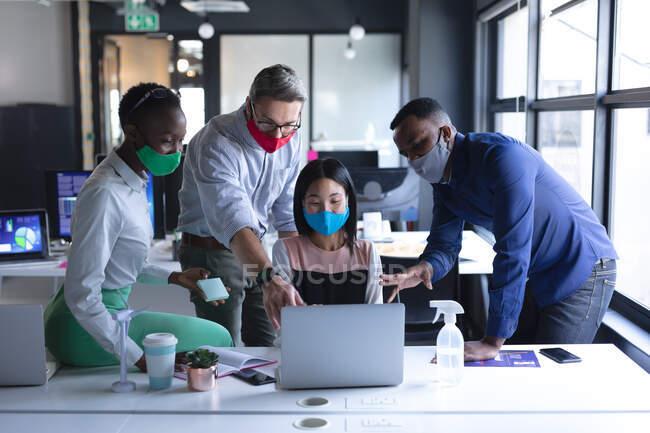 Різні колеги, які носять маску обличчя за допомогою ноутбука, працюючи разом у сучасному офісі. гігієна і соціальна дистанція на робочому місці під час коронавірусу covid 19 пандемії. — стокове фото