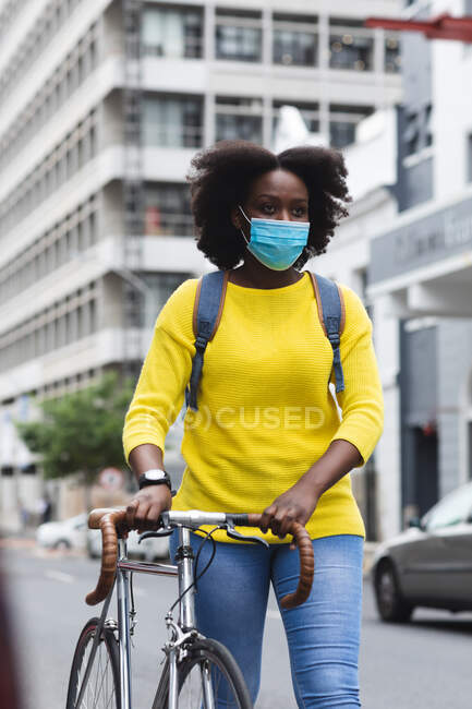African american woman wearing face mask on street carrying her bicycle out and about in the city during covid 19 coronavirus pandemic. — Stock Photo