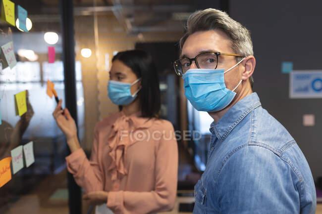 Porträt eines kaukasischen Mannes mit Mundschutz, der in einem modernen Büro steht. Soziale Distanzierung von Quarantäne während der Coronavirus-Pandemie — Stockfoto
