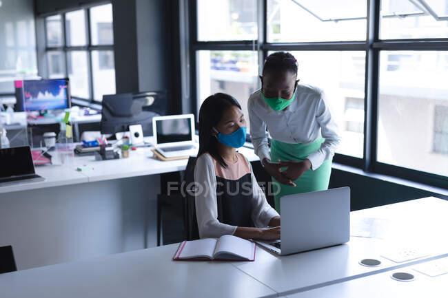 Разнообразные коллеги носят маски для лица, используя ноутбук в современном офисе. социальная изоляция от карантина во время пандемии коронавируса — стоковое фото