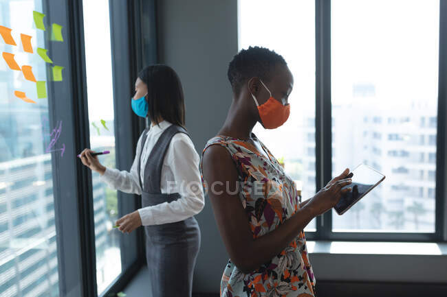 African american woman wearing face mask using digital tablet at modern office. hygiene and social distancing in the workplace during coron — Stock Photo