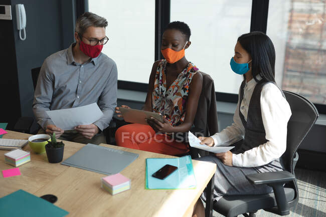 Diverse colleagues wearing face masks laughing together at modern office. social distancing quarantine lockdown during coronavirus pandemic — Stock Photo