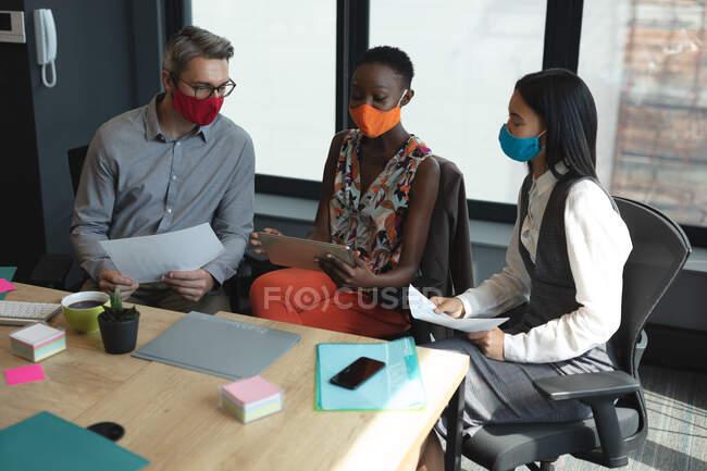 Различные коллеги в масках смеются вместе над современным офисом. социальная изоляция от карантина во время пандемии коронавируса — стоковое фото