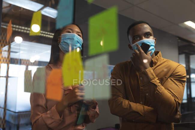 Un homme afro-américain et une femme asiatique portant des masques faciaux discutant de notes de service sur un panneau de verre dans un bureau moderne. hygiène sur le lieu de travail pendant la pandémie de coronavirus — Photo de stock