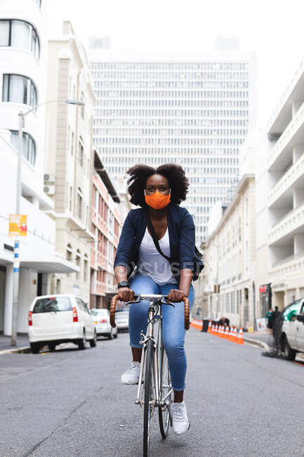 African american woman wearing face mask in street riding a bicycle out and about in the city during covid 19 coronavirus pandemic. — Stock Photo