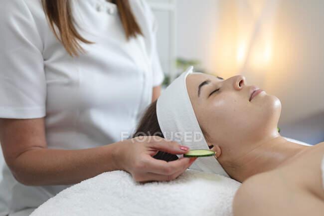 Kaukasische Frau lehnt sich zurück, während Kosmetikerin Gurkenscheiben hält. Kundin genießt Behandlung im Schönheitssalon. — Stockfoto