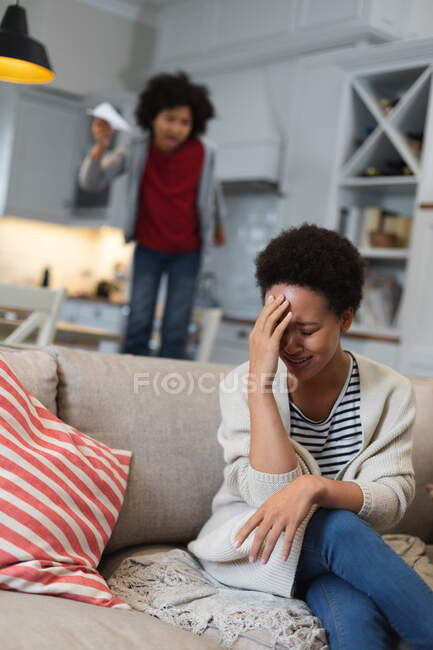 Gemischte Rassenfrau sitzt auf Couch und hält sich die Stirn. Selbst-Isolation Qualität Familienzeit zu Hause zusammen während Coronavirus covid 19 Pandemie. — Stockfoto