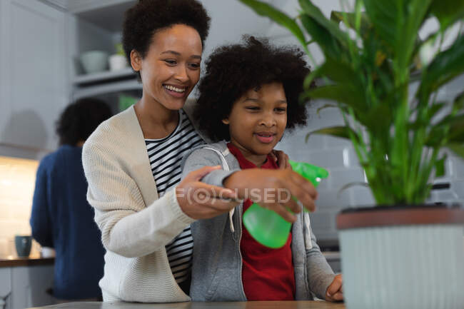 Mixed race woman and daughter watering plants in kitchen. self isolation quality family time at home together during coronavirus covid 19 pandemic. — Stock Photo