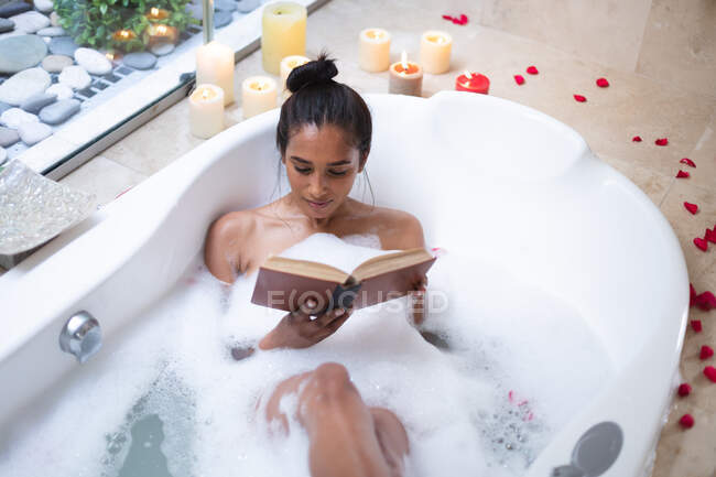 Mixed race woman lying in bath relaxing and reading book. self isolation during covid 19 coronavirus pandemic. — Stock Photo