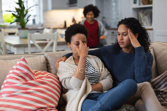 Lésbico de raza mixta molesto sentado en el sofá. hija en el fondo. autoaislamiento calidad familia tiempo en casa juntos durante coronavirus covid 19 pandemia. - foto de stock