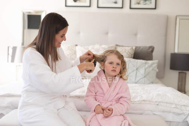 Mulher e filha caucasiana se divertindo no quarto. A mãe está a escovar o cabelo da filha. desfrutando de tempo de qualidade em casa durante coronavírus covid 19 bloqueio pandêmico. — Fotografia de Stock
