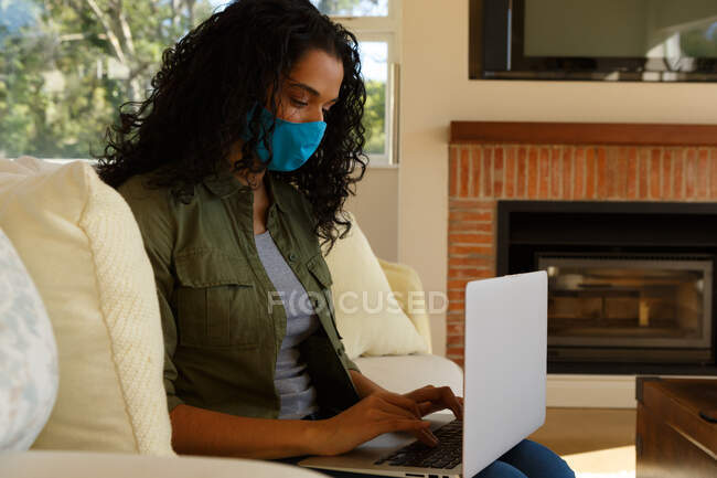 Mujer de raza mixta con máscara usando portátil sentado en el sofá en la sala de estar. autoaislamiento en el hogar durante la pandemia de coronavirus covid 19. - foto de stock