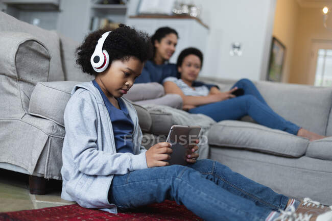 Mixed race girl sitting by couch listening to music using digital tablet. self isolation quality family time at home together during coronavirus covid 19 pandemic. — Stock Photo