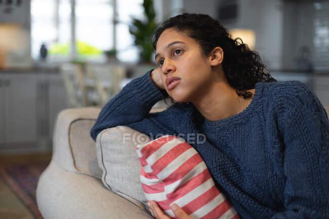 Смешанная расовая женщина сидит на диване и грустит. самоизоляция качество семейное время дома вместе во время коронавируса ковид 19 пандемии. — стоковое фото