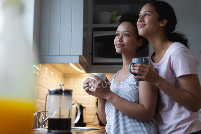 Smiling mixed race lesbian couple drinking coffee and embracing in kitchen. self isolation quality time at home together during coronavirus covid 19 pandemic. — Stock Photo