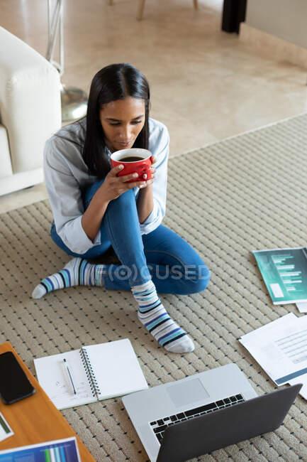 Змішана раса жінка сидить на підлозі і п'є каву вдома. Самоізоляція під час пандемії коронавірусу 19. — стокове фото