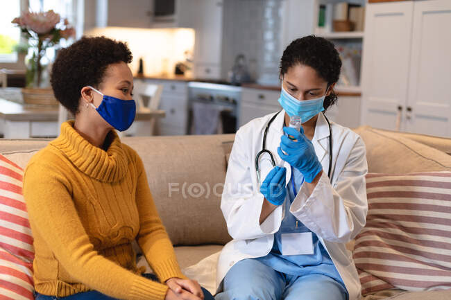 Mulher de raça mista usando máscara facial conversando com uma médica mista sentada no sofá. auto-isolamento em casa juntos durante coronavírus covid 19 pandemia. — Fotografia de Stock