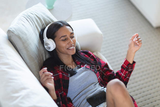 Mixed race woman lying on couch with headphones listening to music at home. self isolation during covid 19 coronavirus pandemic. — Stock Photo